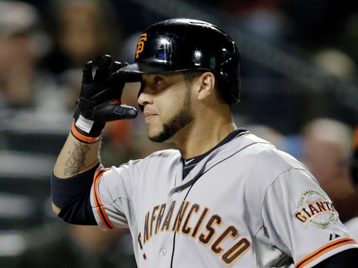 San Francisco Giants Gregor Blanco salutes teammates while crossing home plate after hitting a third-inning two-run home run off New York Mets starting pitcher Aaron Harang in a baseball game on Wednesday, Sept. 18, 2013, in New York. (AP Photo/Kathy Willens)