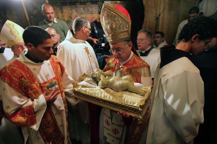Latin Patriarch of Jerusalem Fouad Twal, center, holds the Baby Jesus as he and clergy arrive to pray at the Grotto, traditionally believed by Christians to be the birthplace of Jesus Christ, at the Church of the Nativity, in the West Bank town of Bethlehem, early Tuesday, Dec. 25, 2012. (AP Photo/Abed Al Hashlamoun, Pool) / EPA POOL