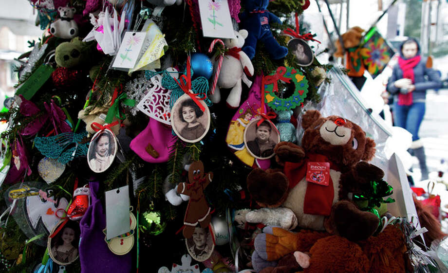 Portraits of slain students and teachers hang from a tree at a memorial in Newtown, Conn. Tuesday, Dec. 25, 2012. People continue to visit memorials in the wake of the shootings after gunman Adam Lanza walked into Sandy Hook Elementary School in Newtown, Conn., Dec. 14, and opened fire, killing 26, including 20 children, before killing himself. (AP Photo/Craig Ruttle) / FR61802 AP
