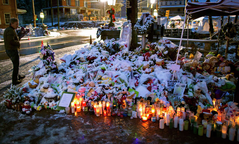 A member of the Rutter family of Sandy Hook, Conn., walks past candles and other offerings that make up a memorial in Newtown, Conn., Tuesday, Dec. 25, 2012. People continue to visit memorials after gunman Adam Lanza walked into Sandy Hook Elementary School in Newtown, Friday, Dec. 14, and opened fire, killing 26, including 20 children, before killing himself. (AP Photo/Craig Ruttle) / FR61802 AP
