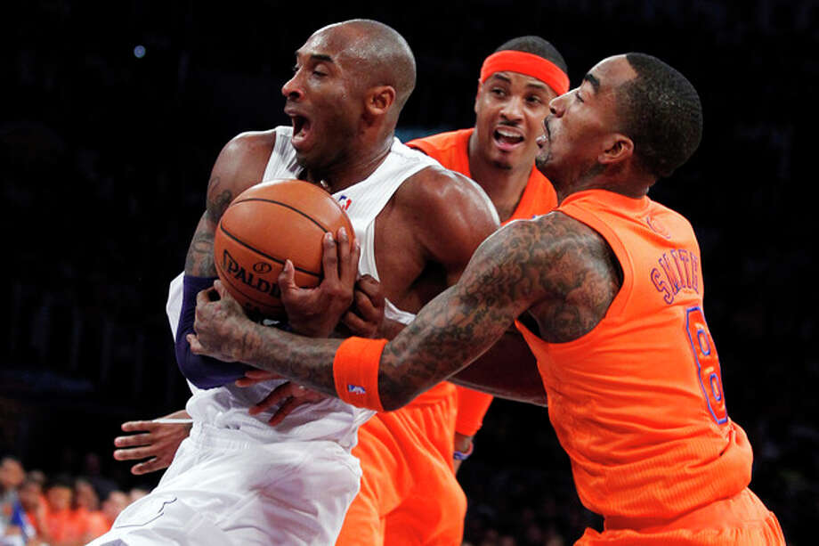Los Angeles Lakers guard Kobe Bryant, left, is fouled by New York Knicks guard J.R. Smith, right, as forward Carmelo Anthony, center, watches during the first half of their NBA basketball game in Los Angeles, Tuesday, Dec. 25, 2012. (AP Photo/Alex Gallardo) / FR170211 AP