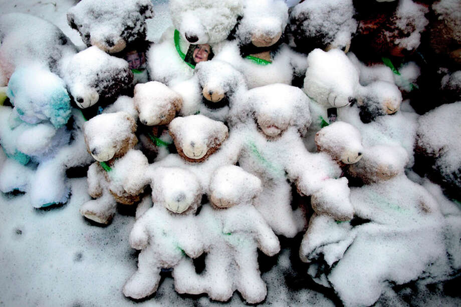 Snow-covered stuffed animals with photos attached sit at a memorial in Newtown, Conn. Tuesday, Dec. 25, 2012. People continue to visit memorials after gunman Adam Lanza walked into Sandy Hook Elementary School in Newtown, Friday, Dec. 14, and opened fire, killing 26, including 20 children, before killing himself. (AP Photo/Craig Ruttle) / FR61802 AP