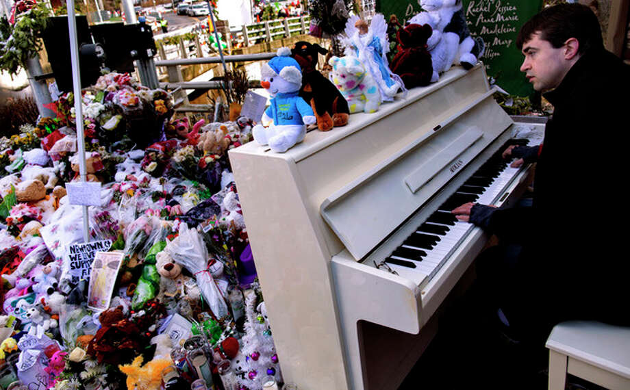 Among a memorial to the Sandy Hook Elementary students and teachers, Julian Revie of Ottawa, Canada, plays Christmas music on a piano he helped bring to the memorial, Tuesday, Dec. 25, 2012 in Newtown, Conn. People continue to visit memorials after gunman Adam Lanza walked into Sandy Hook Elementary School in Newtown, Conn., Dec. 14, and opened fire, killing 26, including 20 children, before killing himself. (AP Photo/Craig Ruttle) / FR61802 AP