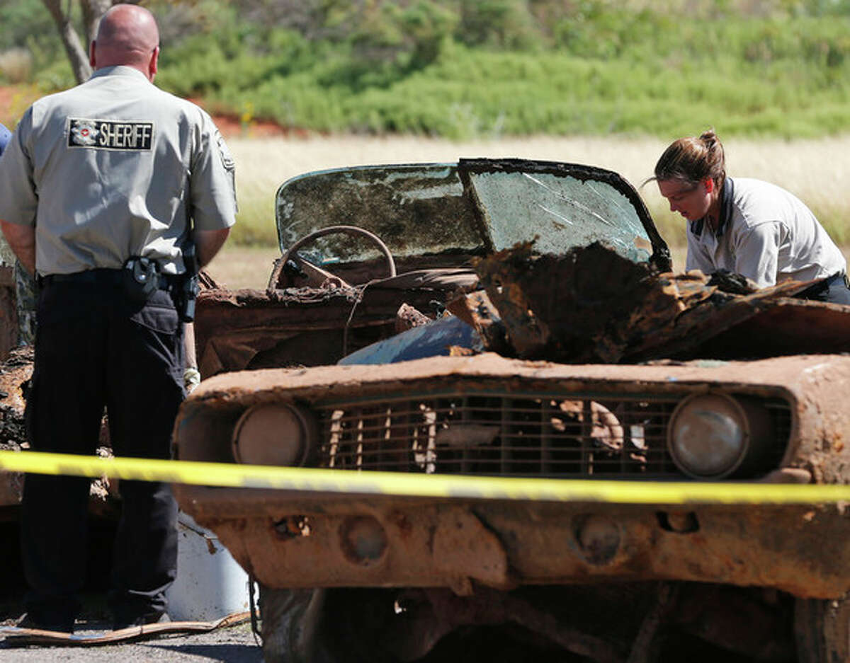 Officials work on the second of two cars found in Foss Lake in Foss, Okla., Wednesday, Sept. 18, 2013. The Oklahoma State Medical Examiner?'s Office says authorities have recovered skeletal remains of multiple bodies in the Oklahoma lake where the cars were recovered. (AP Photo/Sue Ogrocki)