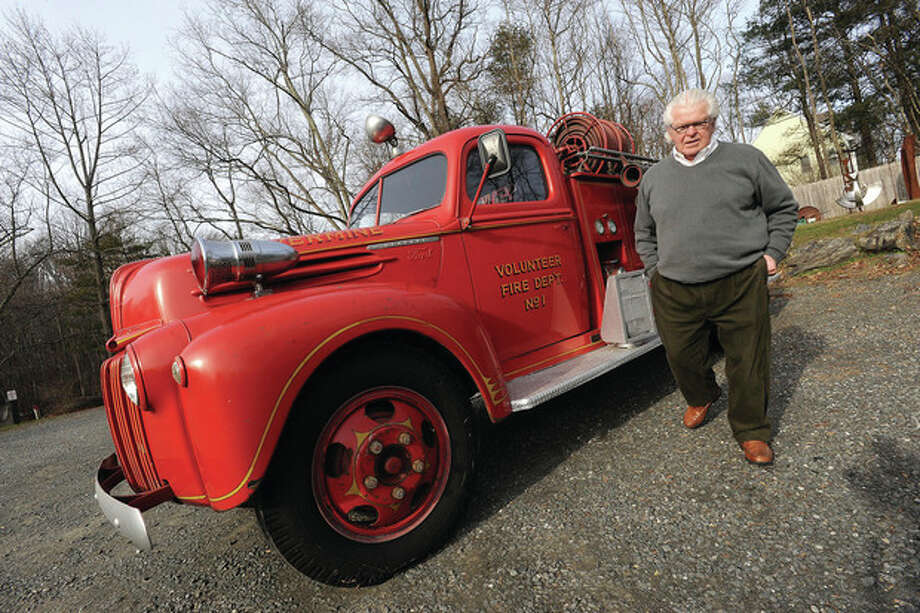 Tom Olson owner of Antiques at the Silvermine Tavern Monday with the 1947 Ford antique firetruck that will be used to bring Santa around the neighborhood for the Silvermine Community Associations Christmas Eve. hour photo/Matthew Vinci