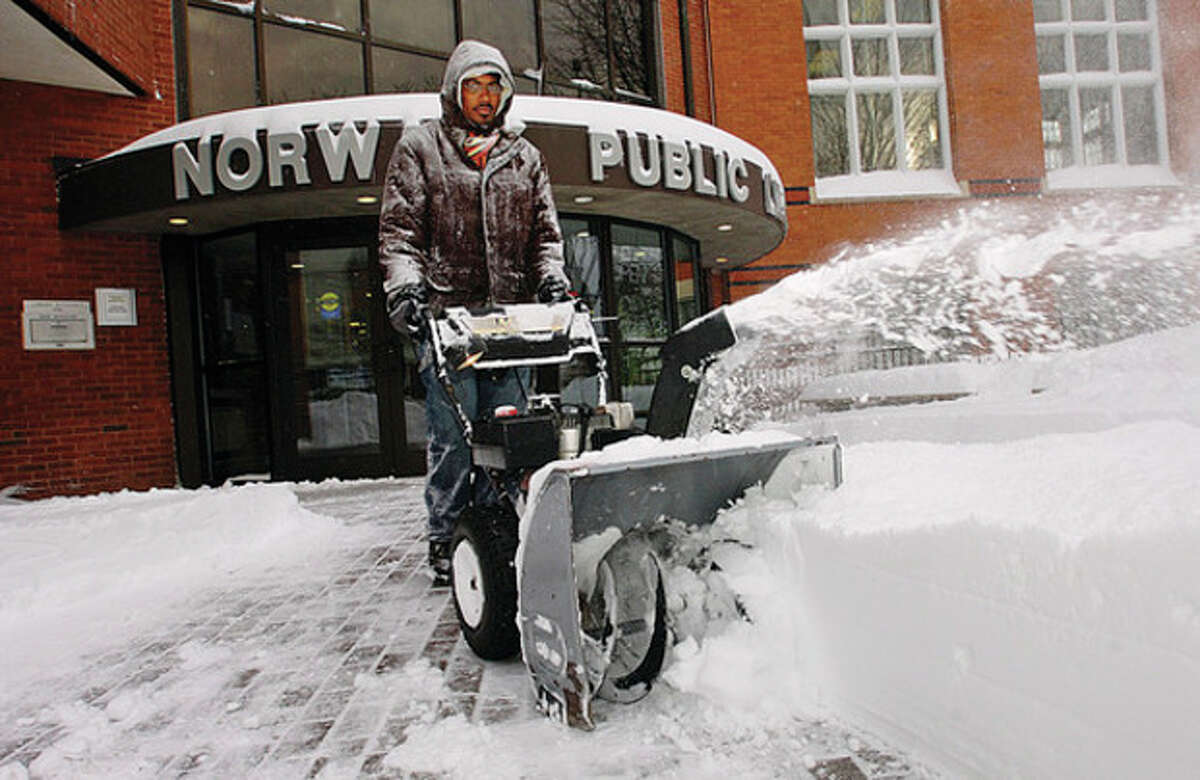 Norwalk library employee Collinn Pratt clears snow from in front of the library on Belden Ave Wednesday morning. Hour photo / Erik Trautmann