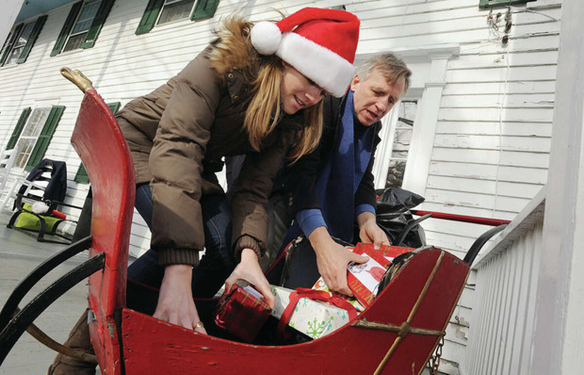 Hour photos/Matthew Vinci Elves visit Silvermine Elf volunteers, Lee Colihan and her father Jim load up donated toys Monday at the Silvermine Tavern. The Silvermine Community Association does their annual Christmas Eve celebration including a visit from Santa on an antique firetruck. At right, Tom Olson owner of Antiques at the Silvermine Tavern Monday with the 1947 Ford antique firetruck that will be used to bring Santa around the neighborhood for the Silvermine Community Associations Christmas Eve.