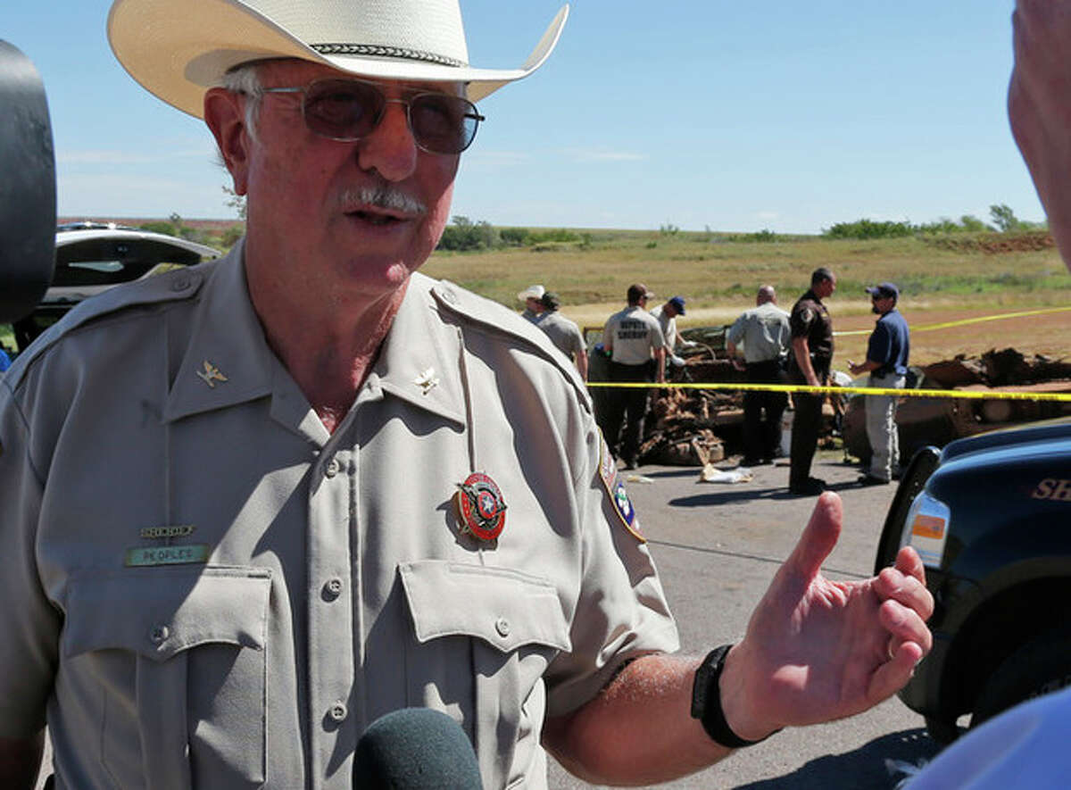 Custer County Sheriff Bruce Peoples answers questions as investigators work on two cars found a day earlier in Foss Lake, in Foss, Okla., Wednesday, Sept. 18, 2013. The Oklahoma State Medical Examiner?'s Office says authorities have recovered skeletal remains of multiple bodies in the Oklahoma lake where the decades-old cars were recovered. (AP Photo/Sue Ogrocki)