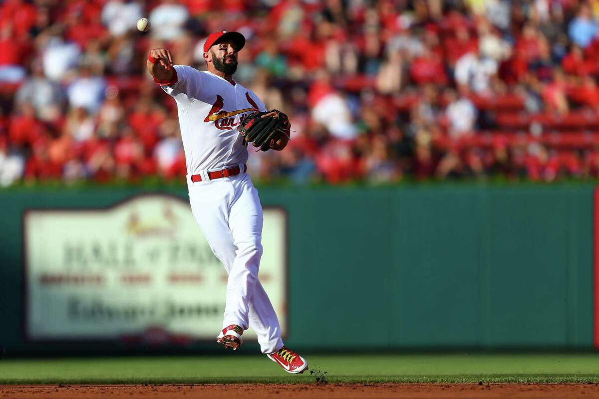 ST. LOUIS, MO - JUNE 15: Matt Carpenter #13 of the St. Louis Cardinals attempts to throw a runner out against the Houston Astros in the second inning at Busch Stadium on June 15, 2016 in St. Louis, Missouri.