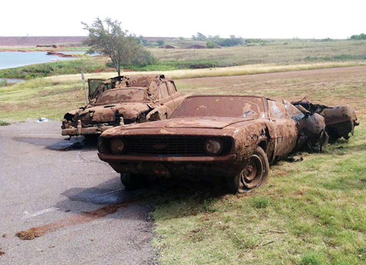 This Sept. 17, 2013, photo shows two cars recovered from Foss Lake, Okla. The Oklahoma State Medical Examiner?'s Office says authorities have recovered skeletal remains of multiple bodies in the Oklahoma lake where the two decades-old cars were pulled from the water by a dive team. (AP Photo/Daily Elk Citian, Laura Eastes)