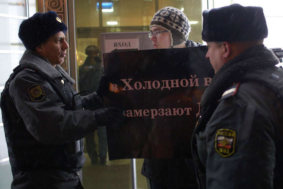"A protester argues with police officers outside the Federation Council on Wednesday, Dec. 26, 2012. Several protesters were detained Wednesday morning outside the upper chamber of Russia's parliament as it prepared to vote on a controversial measure banning Americans from adopting Russian children. The poster held by the protester reads: ""Children get frozen in the Cold War."" (AP Photo/Alexander Zemlianichenko) / AP"