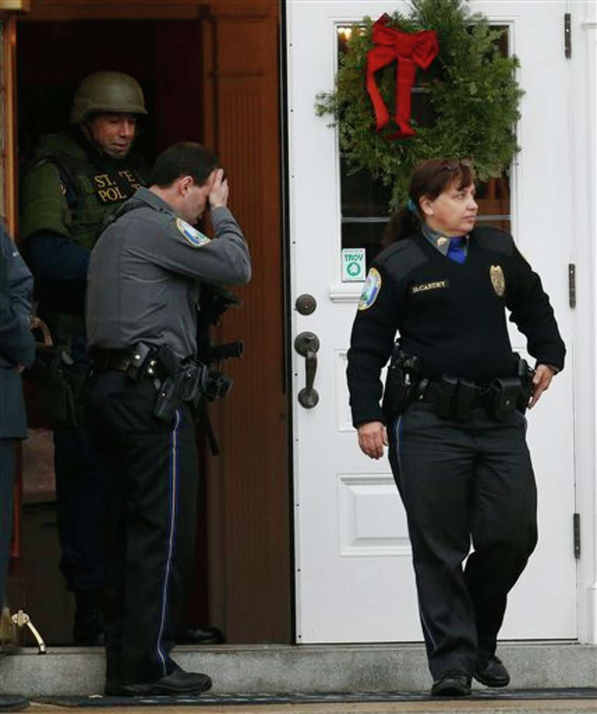 A Newtown Police officer, center, reacts as officer Maryhelen McCarthy, right, walks outside of St. Rose of Lima Roman Catholic Church while responding to a bomb threat, Sunday, Dec. 16, 2012, in Newtown, Conn. Worshippers hurriedly left the church Sunday, not far from where a gunman opened fire Friday inside the Sandy Hook Elementary School in Newtown. (AP Photo/Julio Cortez)