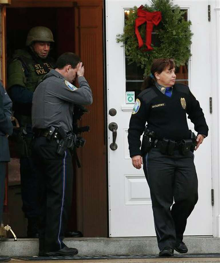 A Newtown Police officer, center, reacts as officer Maryhelen McCarthy, right, walks outside of St. Rose of Lima Roman Catholic Church while responding to a bomb threat, Sunday, Dec. 16, 2012, in Newtown, Conn. Worshippers hurriedly left the church Sunday, not far from where a gunman opened fire Friday inside the Sandy Hook Elementary School in Newtown. (AP Photo/Julio Cortez) / 2012 AP