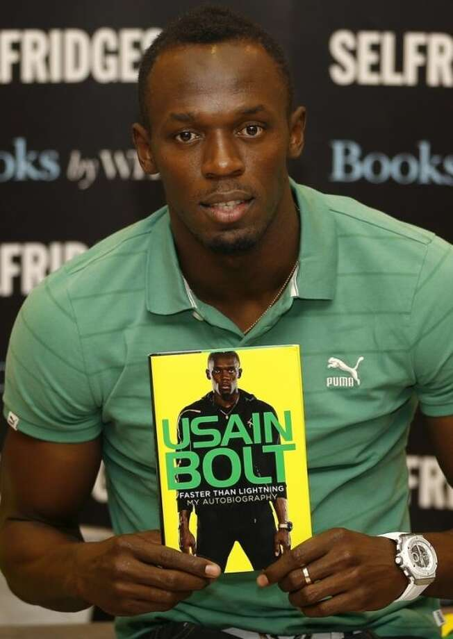 Usain Bolt, Jamaican athlete, poses for the media with a copy of his new autobiography called 'Faster than Lightning' at a department store in London, Thursday, Sept. 19, 2013. (AP Photo/Kirsty Wigglesworth)