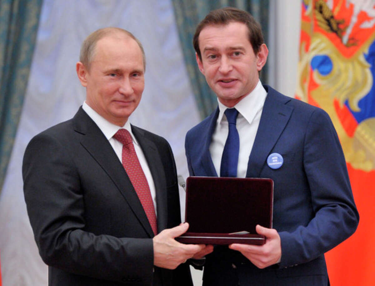 Russian President Vladimir Putin, left, presents a state award to famous Russian actor Konstantin Khabensky wearing a badge that reads