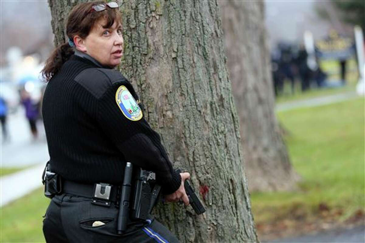 Connecticut State Police officers respond to a bomb threat outside of St. Rose of Lima Roman Catholic Church, Sunday, Dec. 16, 2012 in Newtown, Conn. Worshippers hurriedly left the church Sunday, not far from where a gunman opened fire Friday inside the Sandy Hook Elementary School in Newtown. Police later said nothing dangerous was found. (AP Photo/Mary Altaffer)