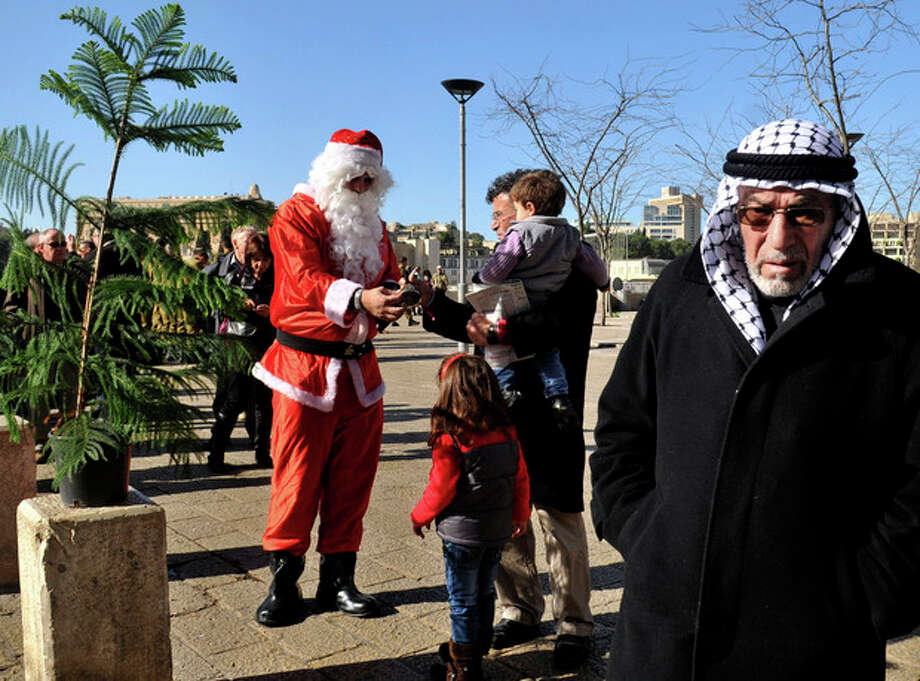 A man dressed as Santa Claus distributes Christmas trees to Christians outside Jaffa Gate in the Old City of Jerusalem, Sunday, Dec. 23, 2012. (AP Photo/Mahmoud Ilean) / AP