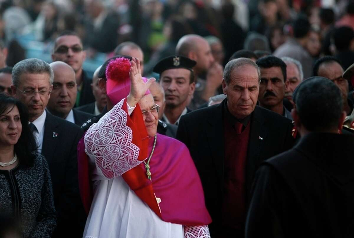 Latin Patriarch of Jerusalem Fouad Twal waves to the crowds before Christmas celebrations in the West Bank town of Bethlehem, Monday, Dec. 24, 2012. Twal, the top Roman Catholic cleric in the Holy Land, has celebrated the United Nations' recent recognition of a Palestinian state in his annual pre-Christmas remarks.(AP Photo/Adel Hana)