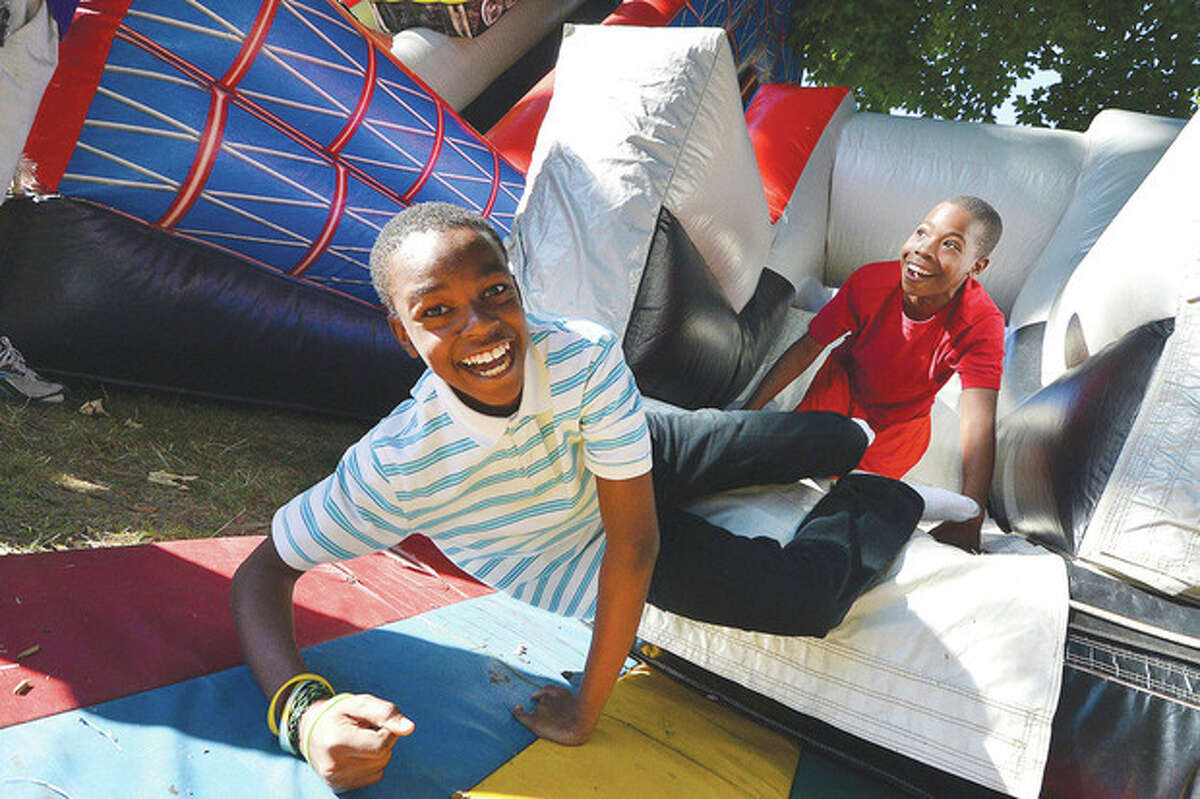 Hour Photo/Alex von Kleydorff Wodney Cadet, 12 and Dior Lopez 11, make it to the bottom of the inflateable obstacle course the 'Wild One' at the 75 year anniversary party at the Carver Center. on Thursday
