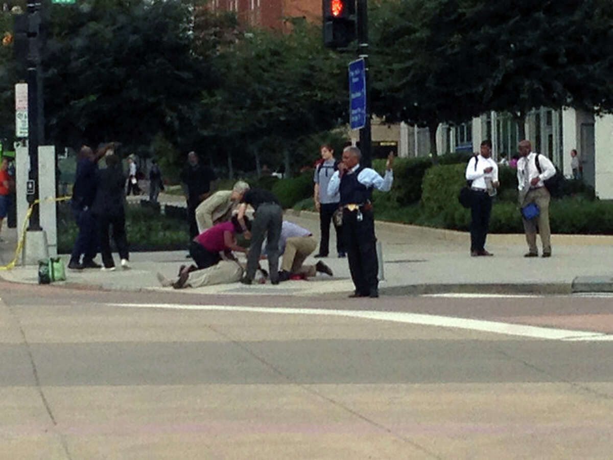 In this photo, which The AP obtained from Don Andres, shooting victim Vishnu Pandit is assisted on the sidewalk while awaiting the arrival of emergency medical personnel after coworkers took him by car from the Washington Navy Yard to receive medical attention Monday, Sept. 16, 2013, in Washington. Pandit died of his injuries. (AP Photo/Don Andres)