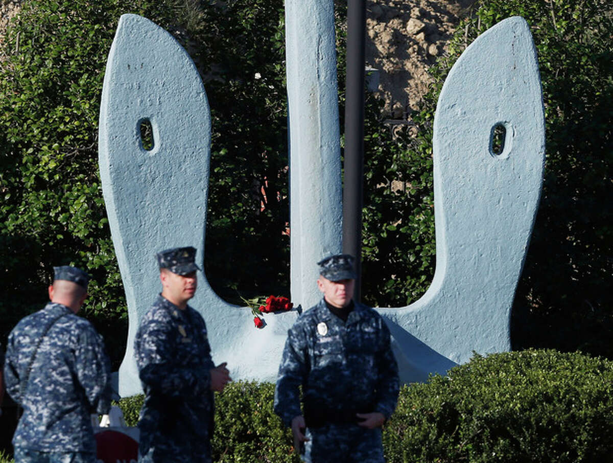 Roses that were placed on an anchor at an entrance of the Washington Navy Yard as security personnel stand watch, Thursday, Sept. 19, 2013. The Washington Navy Yard began returning to nearly normal operations three days after it was the scene of a mass shooting in which a gunman killed 12 people. (AP Photo/Charles Dharapak)