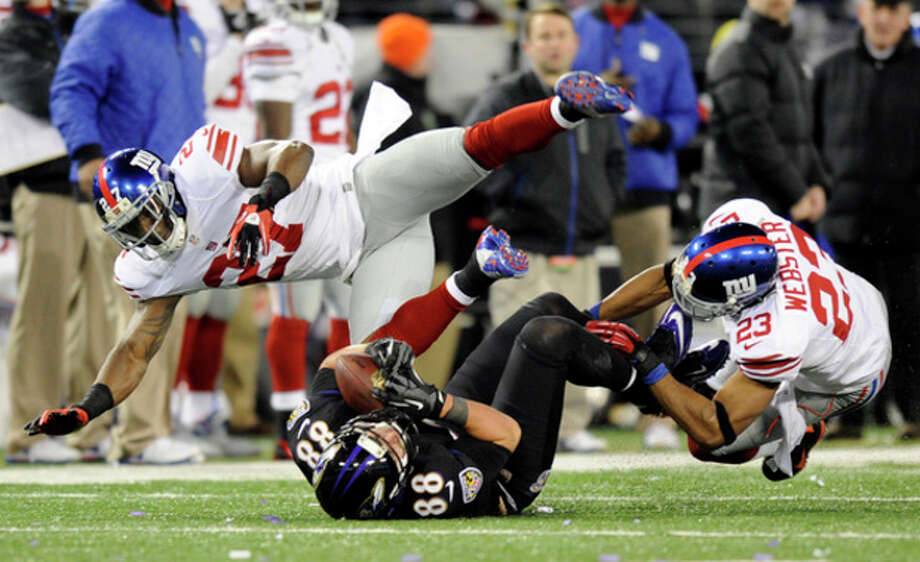 Baltimore Ravens tight end Dennis Pitta, center, makes a catch between New York Giants strong safety Stevie Brown, left, and cornerback Corey Webster in the second half of an NFL football game in Baltimore, Sunday, Dec. 23, 2012. (AP Photo/Nick Wass) / FR67404 AP