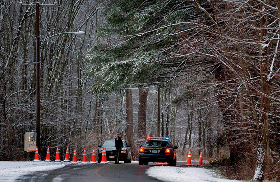 Police continue to block the road to Sandy Hook Elementary School in Newtown, Conn. Tuesday, Dec. 25, 2012. On Tuesday police officers from elsewhere are on duty, to give local officers a break on Christmas. (AP Photo/Craig Ruttle) / FR61802 AP