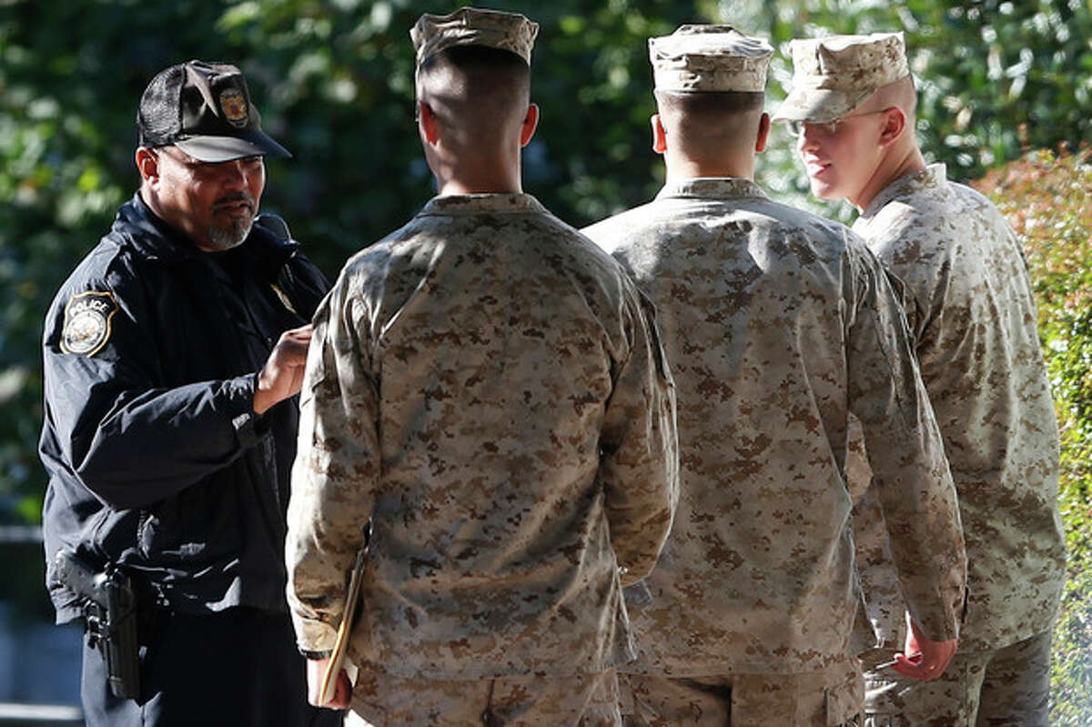 Military personnel have their identification checked after they enter the Washington Navy Yard Thursday, Sept. 19, 2013. The Washington Navy Yard began returning to nearly normal operations three days after it was the scene of a mass shooting in which a gunman killed 12 people. (AP Photo/Charles Dharapak)
