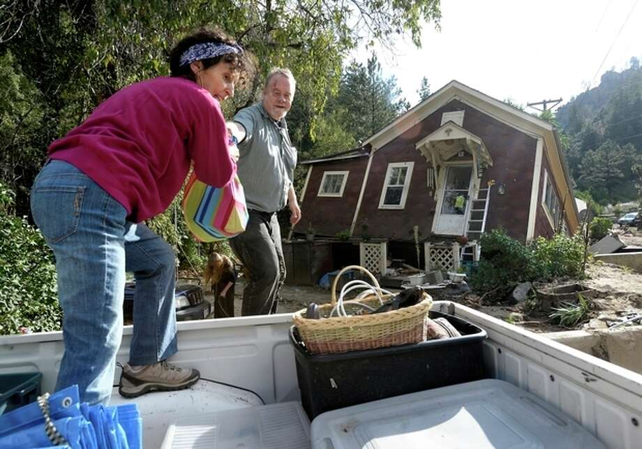 Shireen Malik, left, and Bruce Orr help salvage belongings out of the home of Kathleen McLellan in Salina, Colo., on Thursday, Sept. 19, 2013, in Boulder County. Residents displaced by last week's flooding in the Colorado returned Thursday to salvage what they could from their homes. (AP Photo/The Daily Camera, Jeremy Papasso) NO SALES / Daily Camera