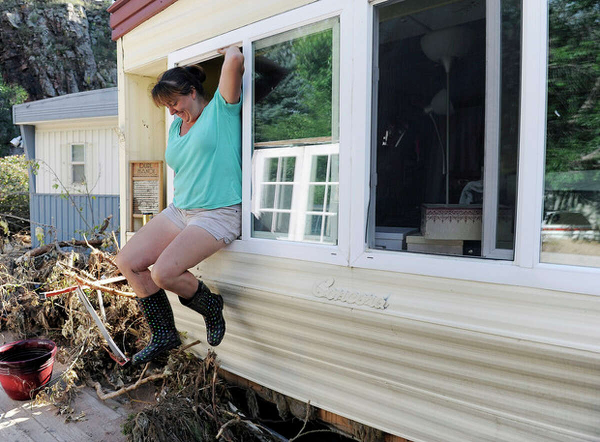 Risa Vandenbos jumps out the window of her flood-damaged trailer at the River Bend Mobile Home Park in Lyons, Colo., on Thursday, Sept. 19, 2013. Vandenbos was gathering belongings that were salvageable from her trailer. Hundreds of evacuees were allowed past National Guard roadblocks Thursday to find a scene of tangled power lines, downed utility poles, and mud-caked homes and vehicles. (AP Photo/Chris Schneider)