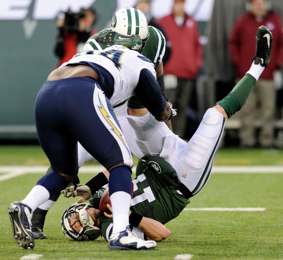 New York Jets quarterback Greg McElroy, bottom, is sacked by San Diego Chargers defensive end Corey Liuget, front left, during the second half of an NFL football game on Sunday, Dec. 23, 2012, in East Rutherford, N.J. The Chargers won 27-17. (AP Photo/Bill Kostroun) / FR51951 AP