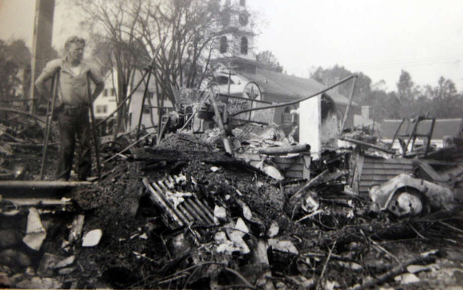 In this photo from the collection of the Monadnock Center for History and Culture, a man stands over debris in downtown Peterborough, N.H. after the Greaty New England Hurricane of 1938. Sept. 21, 1938, Seventy-five years ago the hurricane was estimated to have killed between 682 and 800. It remains the most powerful and deadliest hurricane in recent New England history. (AP Photo/Monadnock Center for History and Culture) / Monadnock Center for History and Culture
