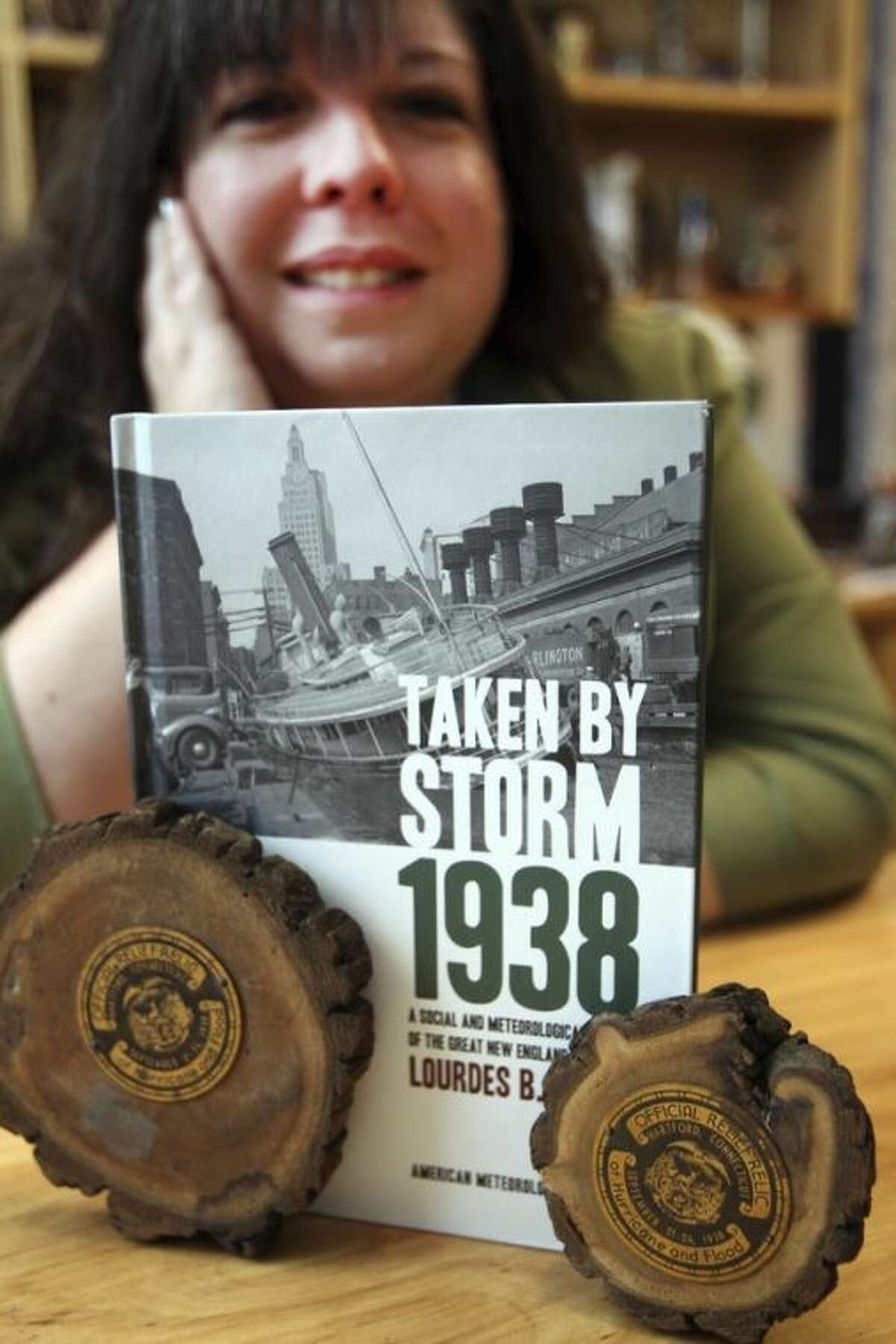 In this photo taken Tuesday, Sept. 17, 2013 in Plymouth, N.H. Plymouth State University meteorology professor Lourdes Aviles poses in front of her book about The Great New England Hurricane of 1938. The hurricane hot New England 75-years ago, Sept. 21, 1938. Seventy-five years later, Aviles said New England could never again be ambushed by a surprise hurricane, given today's forecasting technology. (AP Photo/Jim Cole)