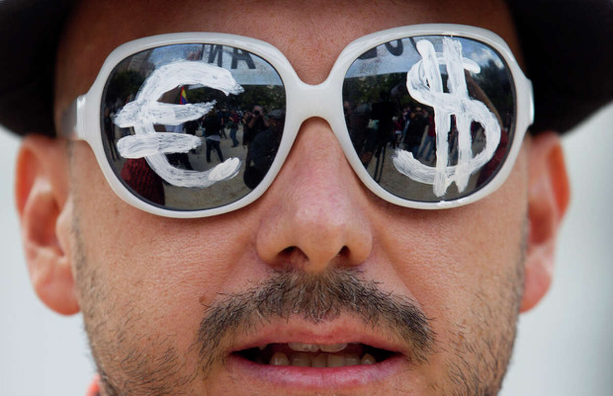 FILE - In this Tuesday, Sept. 25, 2012 file photo, a protester wears glasses with the euro and dollar symbols painted on the lenses before protesting the conservative government's handling of the economic crisis and to demand fresh elections, in Madrid. Many had hoped that 2012 would be the year when the global economy finally regained its vigor, but the three largest economies: The United States, China and Japan struggled, while the 17 countries that use euro endured a third painful year in their financial crisis and slid into recession, and emerging economies slowed. (AP Photo/Paul White, File)