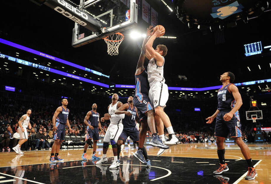 Brooklyn Nets' Brook Lopez (11) shoots over Charlotte Bobcats' DeSagana Diop (2) in the first half of an NBA basketball game on Friday, Dec., 28, 2012 at Barclays Center in New York. (AP Photo/Kathy Kmonicek) / FR170189 AP
