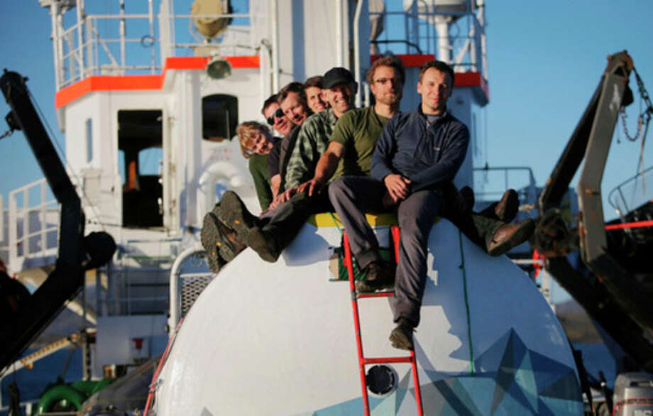 This image made available by environmental organization Greenpeace and taken on Monday, Sept. 9, 2013, shows Greenpeace activists posing atop a 'safety pod' on board of the Arctic Sunrise. The Russian Coast Guard is towing the Greenpeace ship, Arctic Sunrise, toward the nearest port after armed officers stormed it following a protest against oil drilling in Arctic waters. (AP Photo/Denis Sinyakov, Greenpeace) NO SALES, NO ARCHIVE / Greenpeace