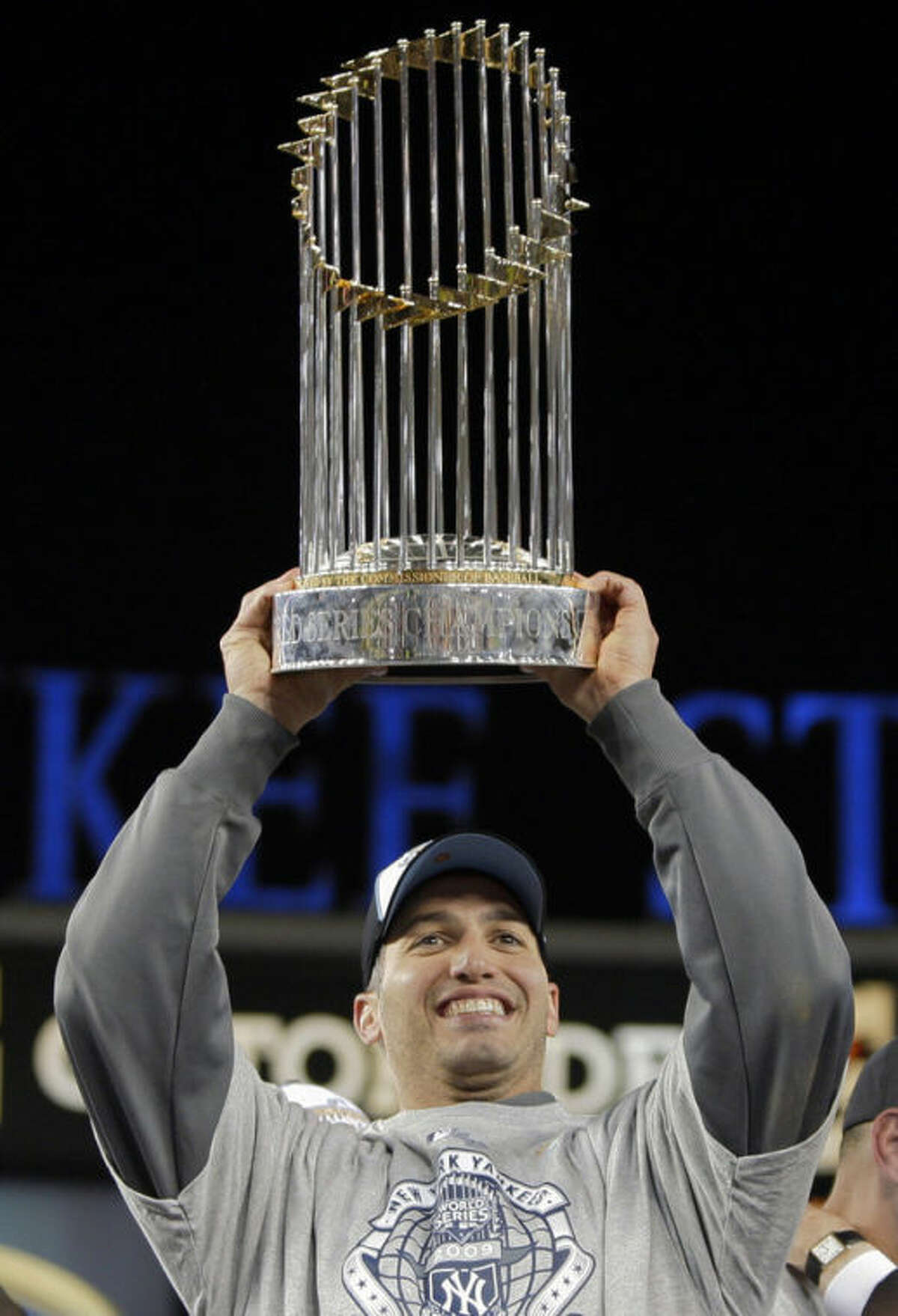 FILE - In this Nov. 4, 2009, file photo, New York Yankees' Andy Pettitte holds up the championship trophy after Game 6 of baseball's World Series against the Philadelphia Phillies in New York. Pettitte is retiring from baseball at the conclusion of the season, the Yankees announced on Friday, Sept. 20, 2013. (AP Photo/Elise Amendola, File)