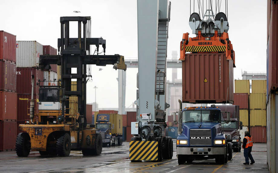 FILE - In this Dec. 18, 2012 file photo, a truck driver watches as a freight container, right, is lowered onto a tractor trailer by a container crane at the Port of Boston in Boston. The crane and a reach stacker, left, are operated by longshoremen at the port. The longshoremen's union may strike if they are unable to reach an agreement on their contract, which expires Dec. 29, 2012. A walkout by dock workers represented by the International Longshoremen's Association would bring commerce to a near halt at ports from Boston to Houston. (AP Photo/Steven Senne, File) / AP