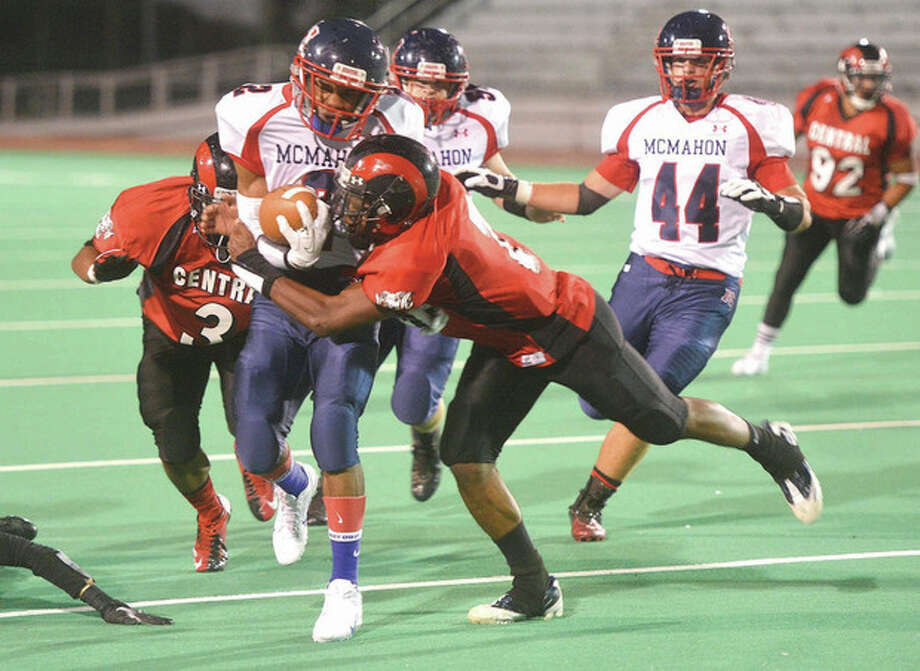 Hour photo/Alex von KleydorffBrien McMahon's Malik Whittaker tries to escape the grasp of a Bridgeport Central defender during Friday night's game at Bridgeport's Kennedy Stadium. McMahon claimed a 20-12 victory.