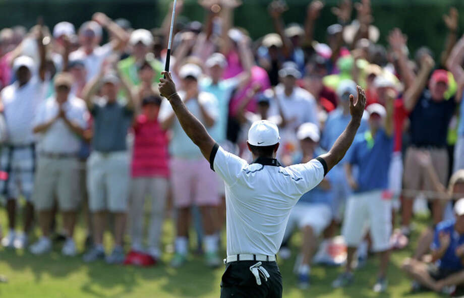 Tiger Woods celebrates with the crowd after making birdie on the third green during the second round of the Tour Championship golf tournament at East Lake Golf Club in Atlanta, Friday, Sept. 20, 2013. .(AP Photo/Atlanta Journal-Constitution, Jason Getz) MARIETTA DAILY OUT; GWINNETT DAILY POST OUT; LOCAL TV OUT; WXIA-TV OUT; WGCL-TV OUT / AJC