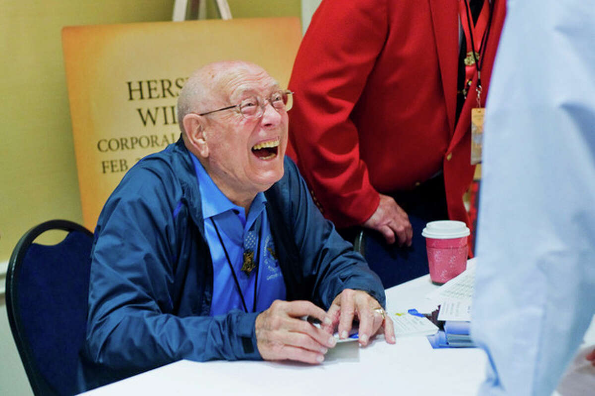 Hershel W. Williams shares a laugh with a conference attendee during the autograph session in Gettysburg, Pa., Thursday, Sept. 19, 2013. Williams was a corporal in the Marine Corps at Iwo Jima during World War II. (AP Photo/The Evening Sun,Clare Becker )