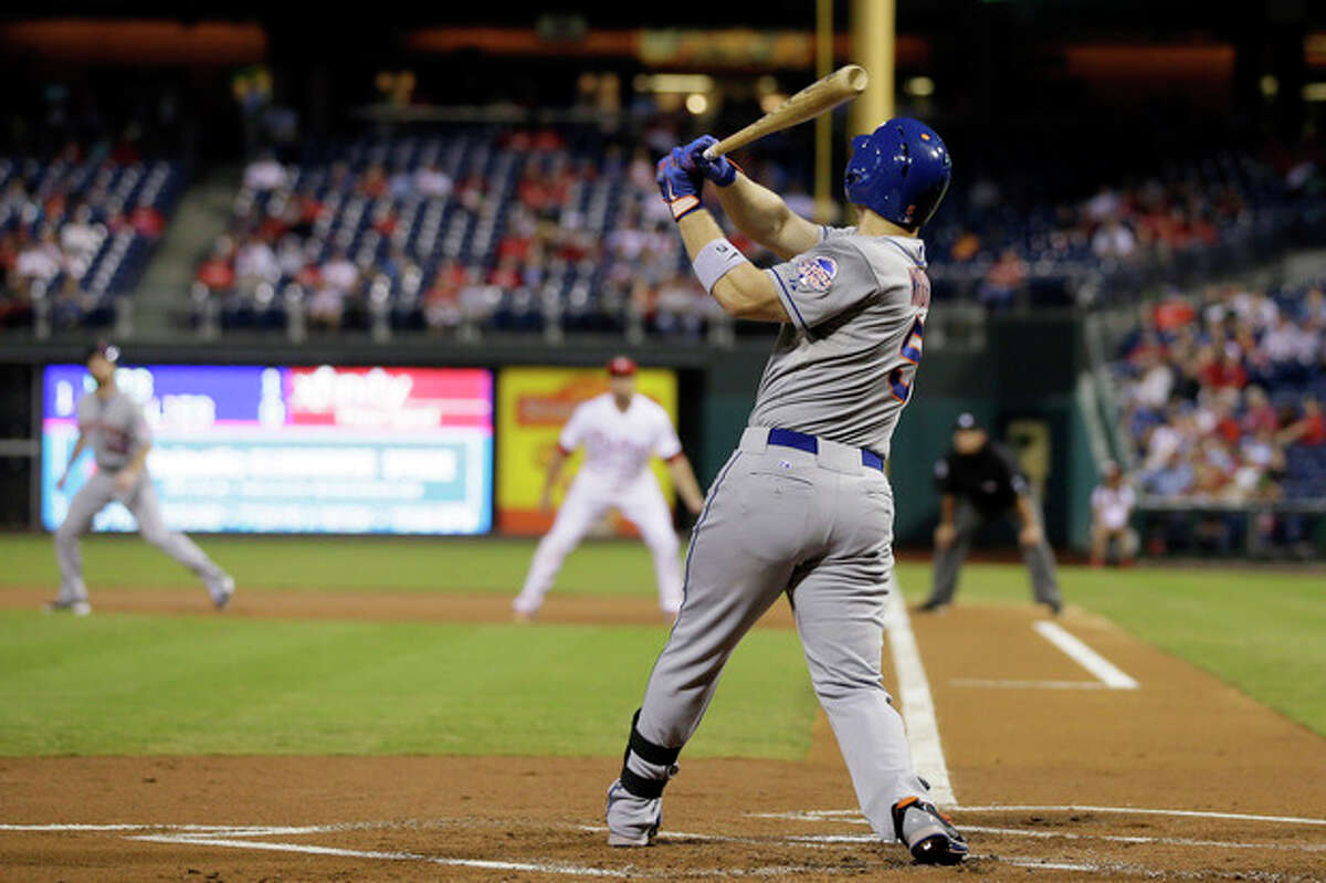 New York Mets' David Wright follows through after hitting a two-run home run off Philadelphia Phillies starting pitcher Cole Hamels during the first inning of a baseball game, Friday, Sept. 20, 2013, in Philadelphia. (AP Photo/Matt Slocum)