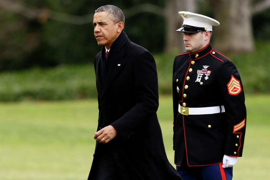 President Barack Obama walks past a Marine honor guard as he steps off the Marine One helicopter and walks on the South Lawn at the White House in Washington, Thursday, Dec. 27, 2012, as he returned early from his Hawaii vacation for meetings on the fiscal cliff. (AP Photo/Charles Dharapak) / AP