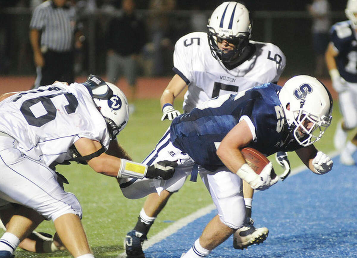 Hour photo/John Nash Staples High running back Patrick Lesch, left, bursts into the end zone for a 5-yard touchdown run before Wilton's Dan Holland, left, and Ethan Segall, top, can make the play on Friday night in Westport. Staples won the game, 14-7.