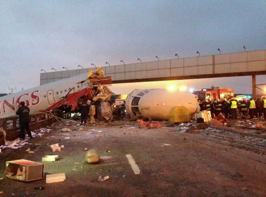 Rescuers work at the site of careered off the runway plane at Vnukovo Airport in Moscow, Saturday, Dec. 29, 2012. A Tu-204 aircraft belonging to Russian airline Red Wings careered off the runway at Russia's third-busiest airport on Saturday, broke into pieces and caught fire, killing several people. (AP Photo/Alexander Usoltsev) / AP