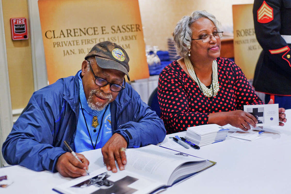 Clarence E. Sasser signs autographs alongside his girlfriend, Patricia Washington, on Thursday, Sept. 19, 2013 in Gettysburg, Pa. Private First Class Sasser served in Vietnam as a combat medic. (AP Photo/The Evening Sun,Clare Becker )