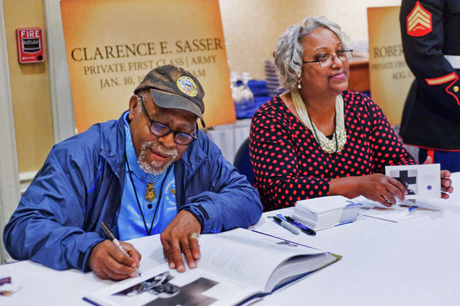 Clarence E. Sasser signs autographs alongside his girlfriend, Patricia Washington, on Thursday, Sept. 19, 2013 in Gettysburg, Pa. Private First Class Sasser served in Vietnam as a combat medic. (AP Photo/The Evening Sun,Clare Becker ) / The Evening Sun