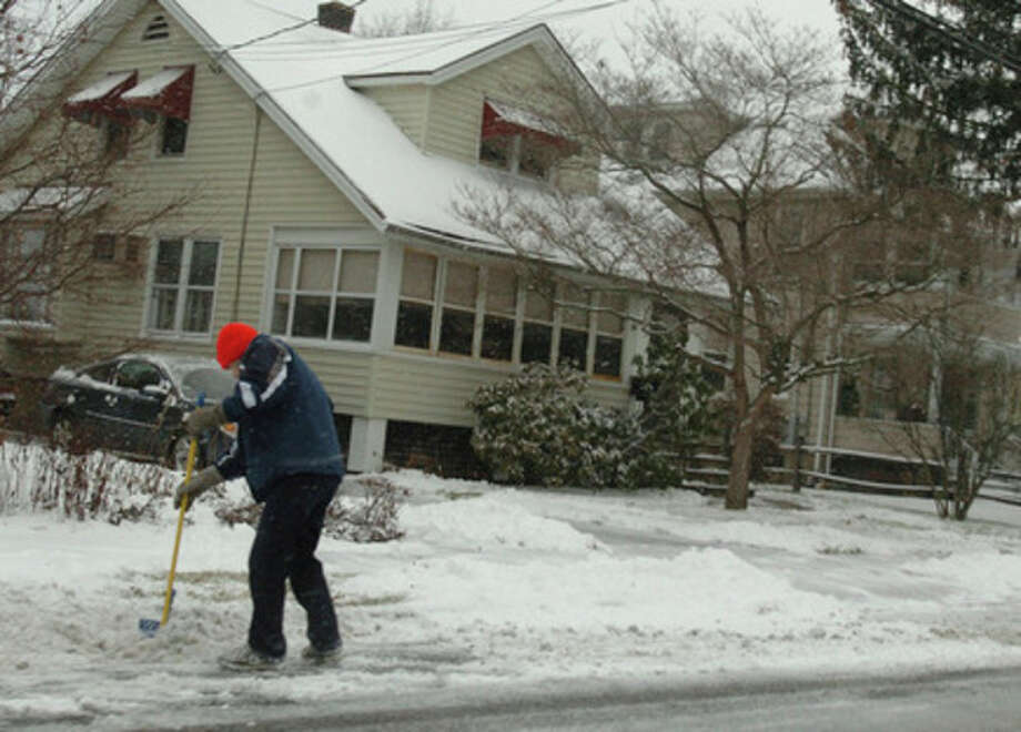 A man shovels the sidewalk on Gregory Boulevard in Norwalk during the snow storm Wednesday afternoon.Hour Photo / DANIELLE ROBINSON