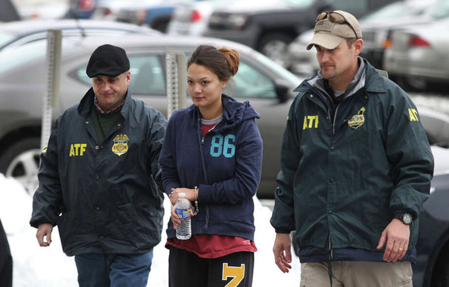 Dawn Nguyen is escorted into the Federal Building, Friday, Dec. 28, 2012, in Rochester, N.Y., and charged in connection with the guns used in the Christmas Eve ambush slaying of two volunteer firefighters responding to a house fire in Webster, N.Y. (AP Photo/Democrat & Chronicle, Jamie Germano) MAGS OUT; NO SALES; MANDATORY CREDIT; INTERNET OUT / Democrat & Chronicle