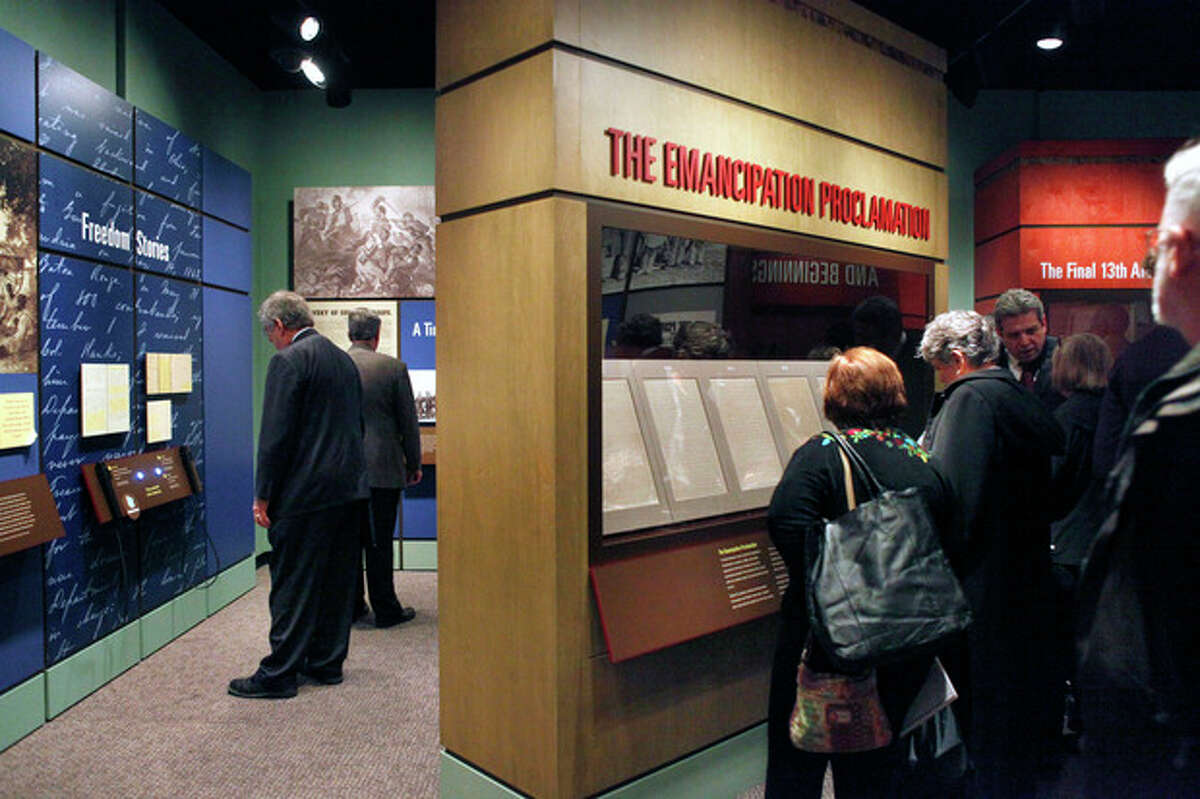 FILE - This Nov 4, 2010 file photo shows National Archives visitors looking at a display of President Abraham Lincoln's Emancipation Proclamation at the National Archives in Washington. As New Year's Day approached 150 years ago, all eyes were on Lincoln in expectation of what he warned 100 days earlier would be coming _ his final proclamation declaring all slaves in states rebelling against the Union to be ?